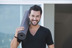 Portrait of a man holding yoga. Mat and smiling Stock Photography