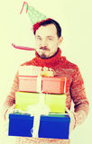 Portrait of Man on holiday in hat and whistle with gifts Royalty Free Stock Image