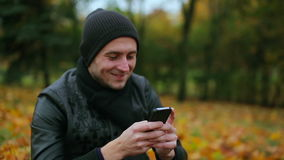 Portrait of a man holiding smartphone typing and chatting sms messages while sitting in the park in autumn - close up stock video footage