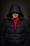 Portrait of a man in a hood with a cigarette Stock Image