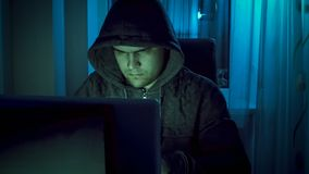 Portrait of young man in hood working on laptop at night. Portrait of man in hood working on laptop at night Stock Image