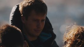 Portrait of man in hooded vest talks with girl and laughing in front of water stock footage