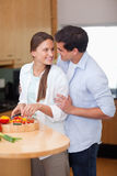 Portrait of a man hugging his wife while she is cooking Stock Images