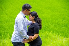 Portrait of a man kiss her pregnant wife, countryside landscape stock photos