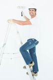 Portrait of man on ladder painting with roller Royalty Free Stock Photo