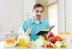 Portrait of man ladle pan and cookbook Stock Photos