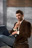 Portrait of man with laptop. Portrait of goodlooking trendy man sitting on office lobby using laptop computer, looking at camera Royalty Free Stock Images