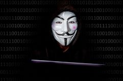 Portrait of man with laptop and vendetta mask isolated on black Stock Photography