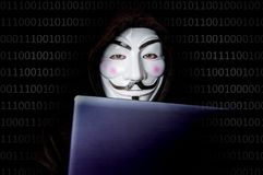 Portrait of man with laptop and vendetta mask isolated on black Royalty Free Stock Photography
