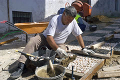 Portrait of man laying new sidewalk, Spain Stock Photo