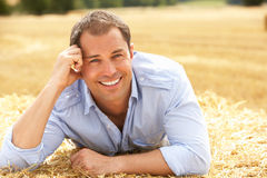 Portrait Of Man Laying In Summer Harvested Field. Smiling At Camera Royalty Free Stock Photo