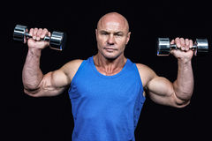 Portrait of man lifting dumbbells with arms raised Stock Photography