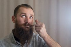 A portrait of a man with a long beard that twists his mustache. A portrait of a white man with a long beard that twists his mustache Royalty Free Stock Image