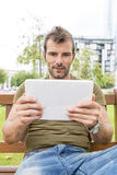Portrait of man looking message in the tablet computer, outdoor. Royalty Free Stock Image