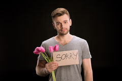 Portrait of man looking to camera while holding tulips bouquet and sorry sign. On black Stock Photography