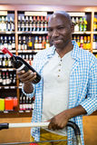 Portrait of man looking at wine bottle in grocery section. At supermarket Royalty Free Stock Photography