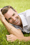 Portrait man lying on grass leaning on elbow Stock Photography