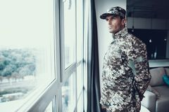 Portrait of Man in Military Uniform Near Window. Serious Confident Thoughtful Person Standing in Modern Apartment Back and Looking at Large Panoramic Window royalty free stock photo