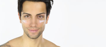 Portrait of a man with moisturizer on her face. Portrait of an handsome guy with moisturizer on her cheeks over a white background Royalty Free Stock Image