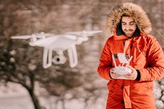 Portrait of man navigating drone over hills and forest - videography and aerial photography concept. Portrait of young man navigating drone over hills and forest royalty free stock photo