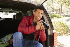 Portrait of man in the open back of car holding camera Royalty Free Stock Images