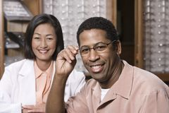 Portrait Of A Man And Optician At Optometrists. Portrait of a happy men and female optician at optometrists Stock Images