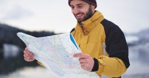 Portrait of a man with orange jacket holding a big map to find his location , he arrived in wonderful place with snowy stock video