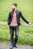 Portrait of a man outdoors. Portrait of a stylish man outdoors at the countryside on the green meadow background stock photo