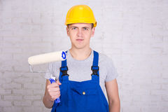 Portrait of man painter in workwear with roller paintbrush over Royalty Free Stock Images