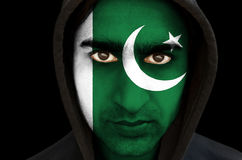 Portrait of a man with Pakistani flag face paint. On black background Royalty Free Stock Image