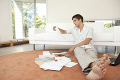 Portrait of Man with Paperwork Sitting on Floor Stock Photo
