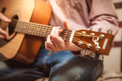 Portrait of man playing on acoustic guitar on sunny day Stock Photography