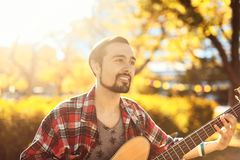 Portrait of man playing bass guitar in the park Stock Image