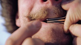 Portrait of a man playing a harp. The bearded shaman plays the harmonica drymba. Face closeup with a musician Jew`s Harp. stock video footage