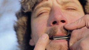 Portrait of a man playing a harp. The bearded shaman plays the harmonica drymba. Face closeup with a musician Jew`s Harp. stock video