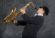 Saxophonist. Portrait of a man playing on saxophone on grey background Royalty Free Stock Image