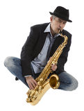 Saxophonist. Portrait of a man playing on saxophone isolated on background Stock Photography