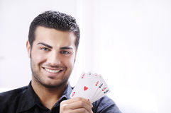 Portrait of man with poker cards. Man with ace poker; four aces in hands; smiling and looking in camera Royalty Free Stock Photography