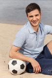 Portrait of man posing on beach with ball. Stock Images