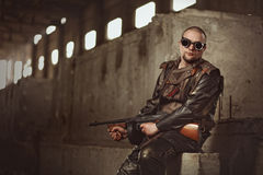 Portrait of a man from post-apocalyptic world with machine gun and the black glasses in an abandoned building Royalty Free Stock Images