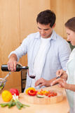 Portrait of a man pouring a glass of wine while his wife is cook Stock Photos