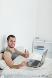 Portrait of a man purchasing online with thumb up Royalty Free Stock Photography