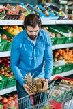 Portrait of man putting fruits into shopping trolley. In grocery shop Royalty Free Stock Image