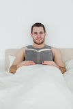 Portrait of a man reading a book. In his bedroom Stock Image