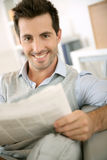 Portrait of man reading newspaper in sofa Stock Photos