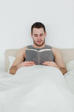 Portrait of a man reading a novel. In his bedroom Royalty Free Stock Images