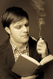 Portrait of a man reading and smoking a pipe Stock Image