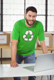 Portrait of man in recycling symbol tshirt working on laptop Royalty Free Stock Photography
