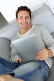 Portrait of man relaxing in sofa with tablet in hands Stock Photos