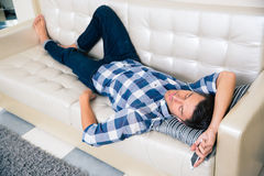 Portrait of a man resting in cloth on the sofa at home Royalty Free Stock Image